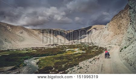 Woman pushing her bicycle uphill on a difficult mountain road on a tibetan plateau leading to the remote Guge Kingdom, Tibet