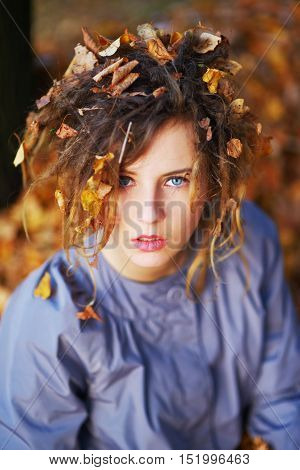 Portrait of young attractive girl with yellow leaves in her hair on autumn background