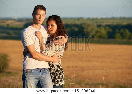 young couple posing on country outdoor in evening, romantic and tenderness concept, summer season