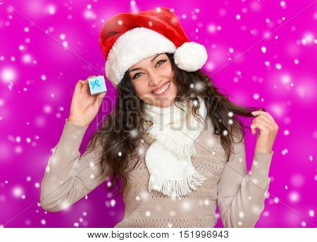 girl in santa hat portrait with little gift box posing on pink color background, christmas holiday concept, happy and emotions