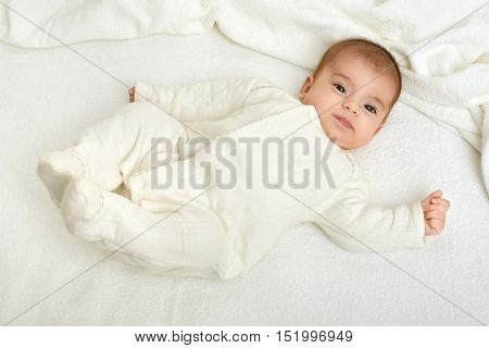 baby on white towel in bed, yellow toned