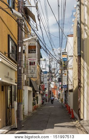 Kyoto Japan - September 16 2016: Street in Gion neighborhood houses multiple bars on top of each other. The entanglement of power and communication cables is standard in Kyoto.