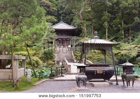 Kyoto Japan - September 16 2016: The Kemuri-Kaburi incense burner stands in front of bridge over pond and a stairway leading to a shrine at Chion-in Buddhist temple. Garden setting.