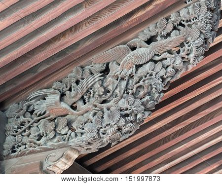 Kyoto Japan - September 16 2016: Detail of elaborate wood carving at Chion-in Buddhist temple ceiling shows flying crane birds above forest scenery.