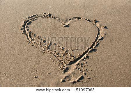Cute hearth shape written in the sand on the beach