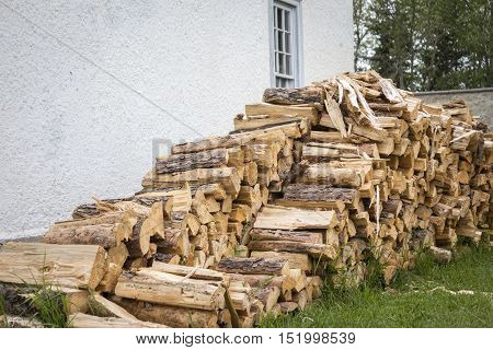 horizontal image of a pile of cut wood  piled up beside the house.