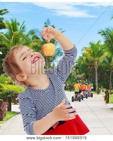 Nice little blonde girl with a red bow on the head holding the tail in front of the face of a delicious Apple . close-up.