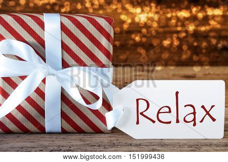 Macro Of Christmas Gift Or Present On Atmospheric Wooden Background. Card For Seasons Greetings, Best Wishes Or Congratulations. White Ribbon With Bow. English Text Relax