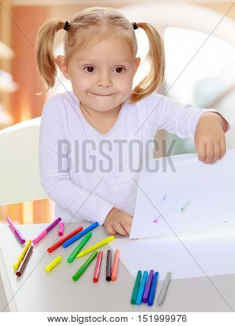 The concept of pre-school education of the child among their peers . in gaming room with a large arched window.Pretty little blonde girl drawing with markers at the table.Girl happily shows