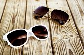 One White Female Sunglasses And One Unisex Sunglasses Close-up On A Wooden Background poster