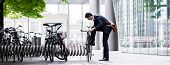 Businessman parking his bicycle in town at a bicycle rack after commuting to work in a concept of ec poster