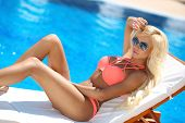 Beautiful Sexy Woman Bikini Model Posing And Tanned On Deck Chair By The Blue Swimming Pool,summer V poster
