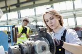 Mature female worker working on machinery with colleague in background at industry poster