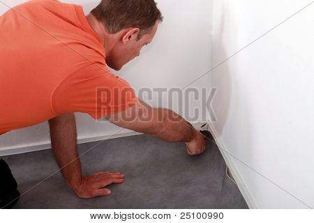 Man laying linoleum flooring
