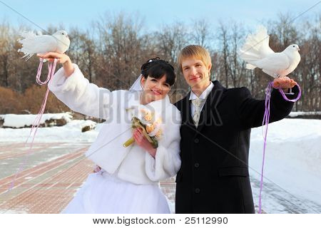 smiling beautiful bride and groom hold white doves at winter outdoors