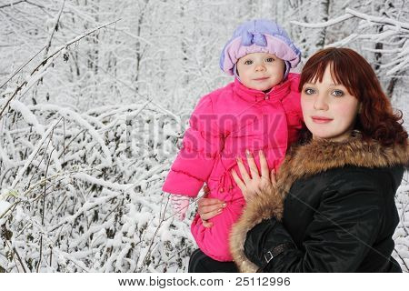 Young beautiful mother with little daughter stands in woods in snow
