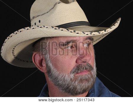 Un hombre con una barba gris en un sombrero vaquero blanco