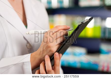 Female pharmacist or assistant is doing inventory or order taking in pharmacy