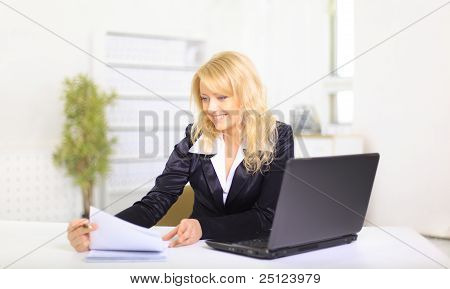 Attractive smiling young business woman using laptop at work in an office