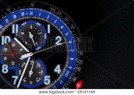 Macro de detalhe de um relógio de pulso cronógrafo sobre um fundo preto couro