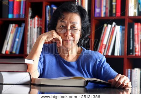 Mature Asian woman reading in the library