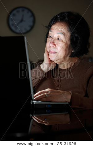 senior asian lady surfing the net late night