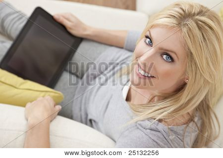 Overhead photograph of a beautiful young women at home sitting on sofa or settee using a tablet PC computer and smiling