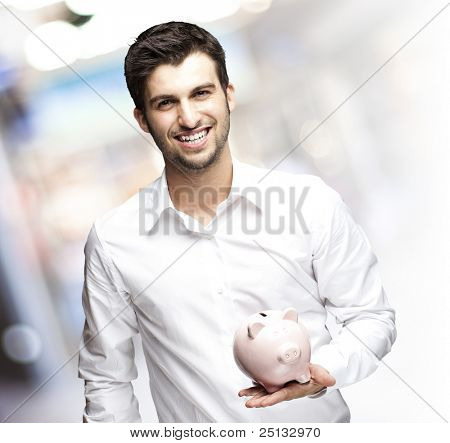 portrait of young man holding a piggy bank against a crowded place