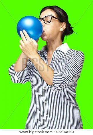 portrait of a middle aged woman blowing a balloon against a removable chroma key background