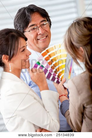 People with an interior designer choosing a new color to decorate the office