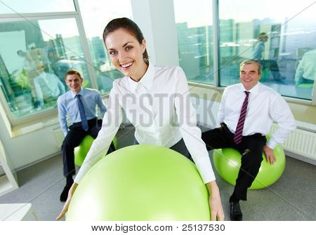 Portrait of pretty female with big ball looking at camera and smiling with her colleagues behind