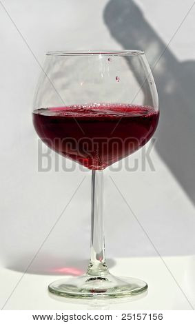 One Glass Of Red Wine With Bottle Shadow
