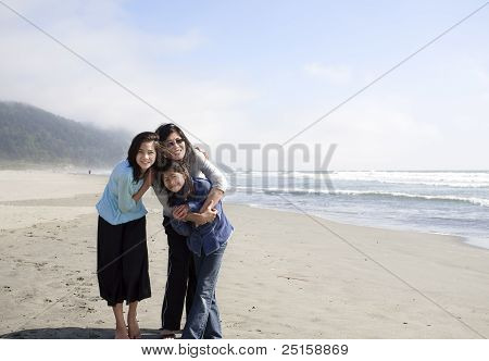 Asian Mother And Two Daughters Smiling On The Beach By Ocean.