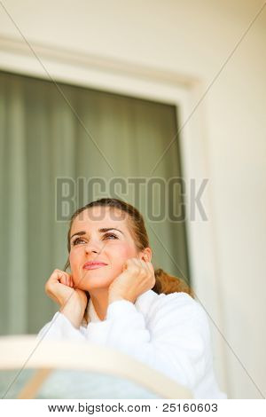 Portrait Of Dreaming Attractive Female In Bathrobe Sitting At Table On Terrace