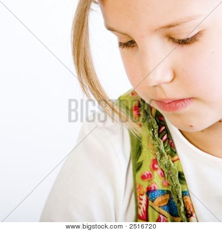 Head Shot Of A Blond Young Girl Looking Down