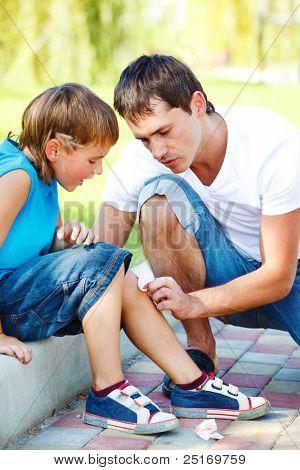 Papá ayudar a niño para limpiar la sangre de su pierna lesionada