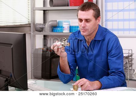 Plumber looking at a joint in a stockroom