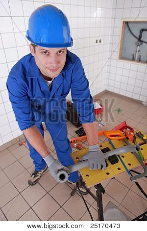 Plumber measuring plastic piping