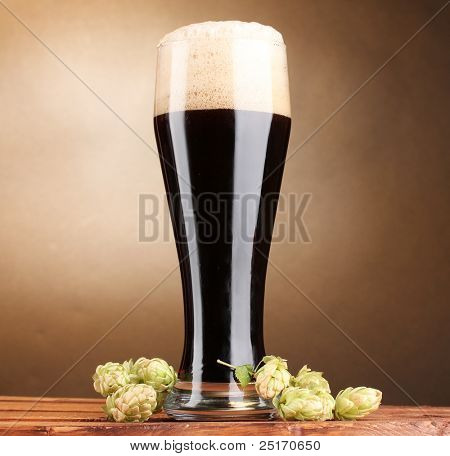 dark beer in glass and green hop on wooden table on brown background