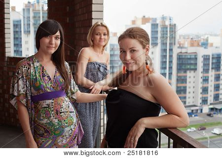 Three Young Caucasian Women Standing On Balcony