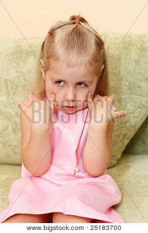 Little Child A Girl In Pink Dress Sitting On Sofa In Domestic Room And Making Faces.