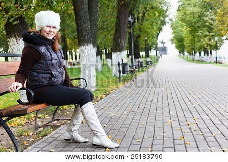 Young beautiful woman sitting alone on a park bench