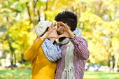 Dating And Autumn Love Concept. Couple In Love With Scarves Shows Heart Sign With Fingers. Girl And  poster