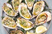 Barbecue overbaked fresh opened oyster with garlic, lemon and herbs offered as top view on a plate poster