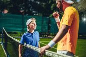 Laughing Child Looking At Glad Trainer While Speaking With Him. Cheerful Man Holding Sport Equipment poster