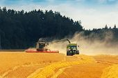 Crop Harvest - Combine Harvester Loading Grains In A Tractor Trailer On The Field poster