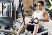Portrait of a determined handsome young man looking forward while rowing at the cable machine during poster