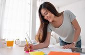 Asian Female Freelancer Standing And Writing On Paperwork Working On Table In Bedroom At Home.work A poster