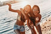So Much Fun Together. Two Attractive Young Women In Swimwear Smiling While Spending Carefree Time On poster