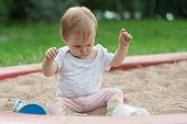 A Little Girl Is Sitting In A Sandbox On The Sand And Playing With Sand. The Kid Takes The Sand In T poster